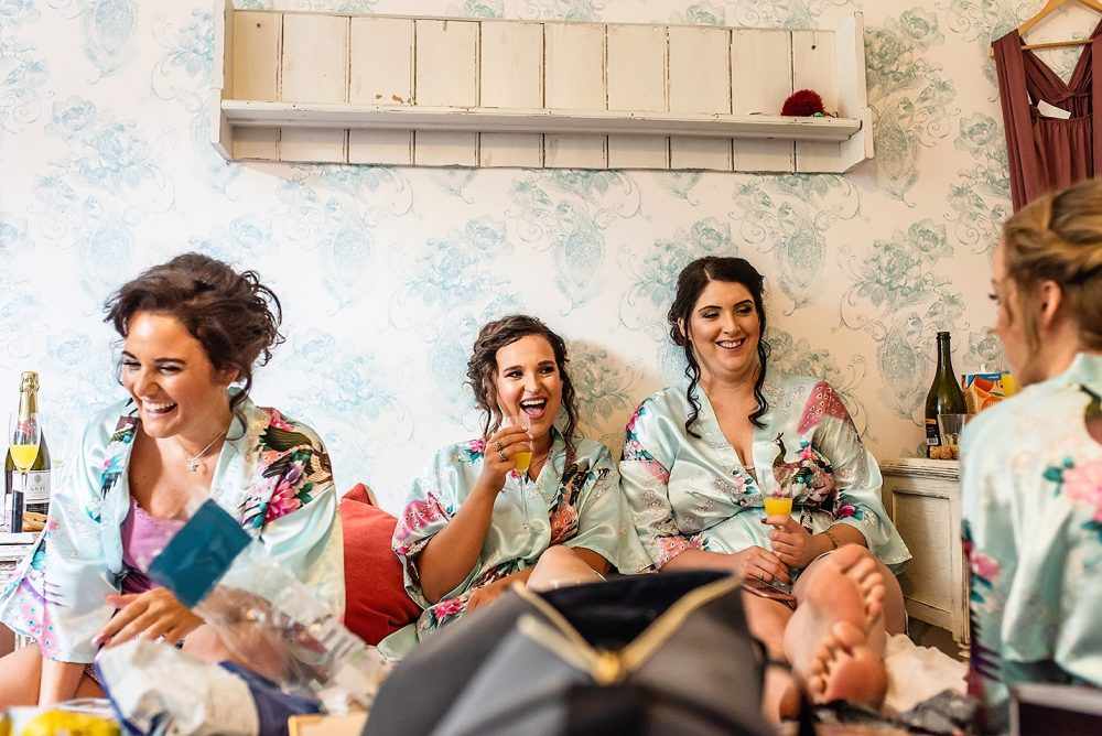 bride and bridesmaids laughing while getting ready by documentary wedding photographer in South London and Kent