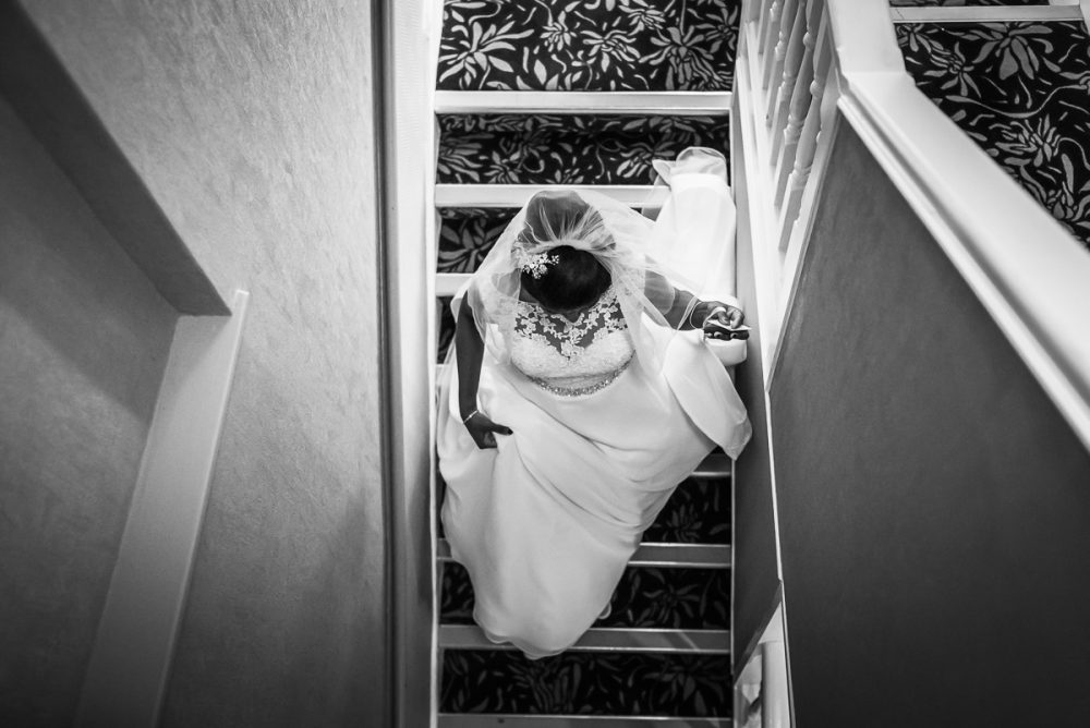 black and white image of bride going downstairs to the ceremony by documentary wedding photographer in South London and Kent