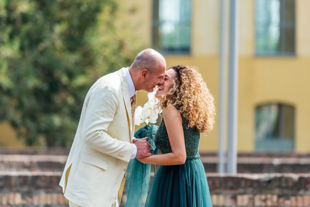bride in green wedding dress with groom in white suit by documentary wedding photographer in South London and Kent