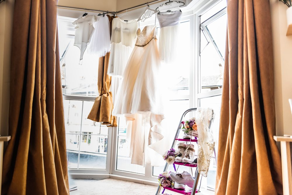 wedding dress hanging ready for bride to dress by documentary wedding photographer in South London and Kent