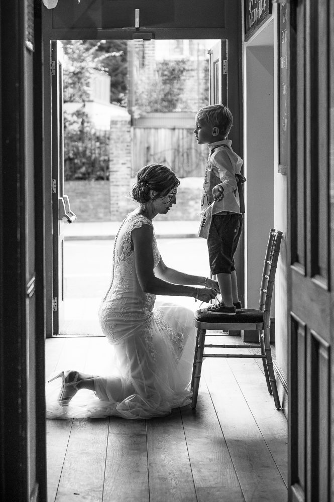 bride lacing the shoes of a page boy by Wedding Photographer South London