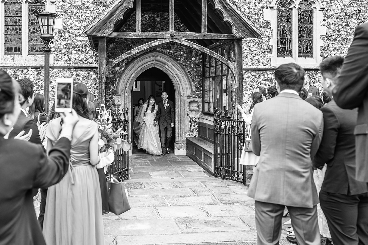 Newlywed couple coming out of the church by Wedding photographer in Kent