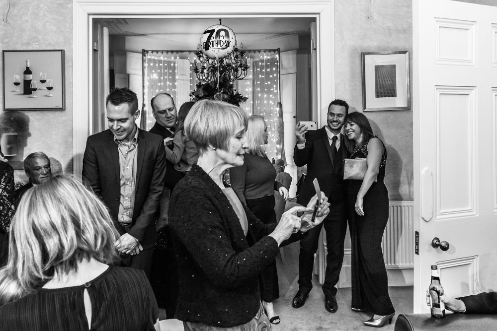 guests at a party taking selfies by Wedding Photographer South London