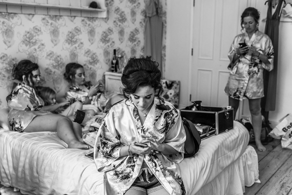 Bride and Bridesmates looking at the phone during preparation by wedding photographer in Kent and South London