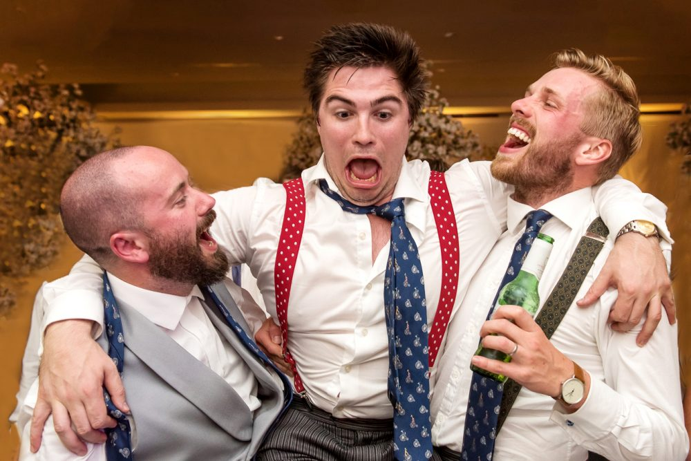 Groom and mates dancing the dancefloor by Wedding Photographer in South London