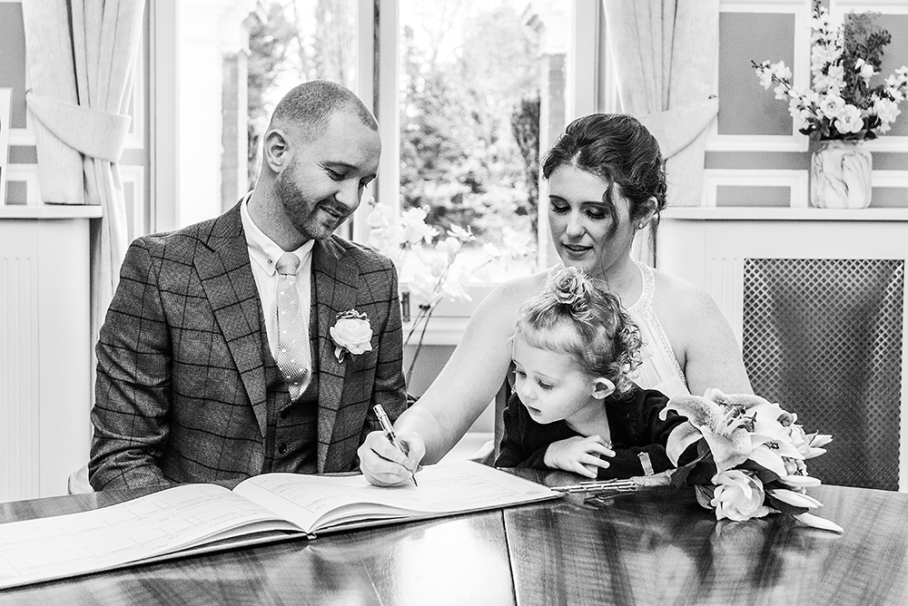 Couple signing the registry at the Old Palace Bromley Registry Office