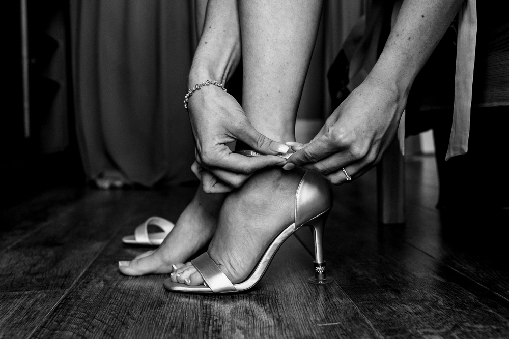 Bride putting her wedding shoes on by South London Wedding Photographer